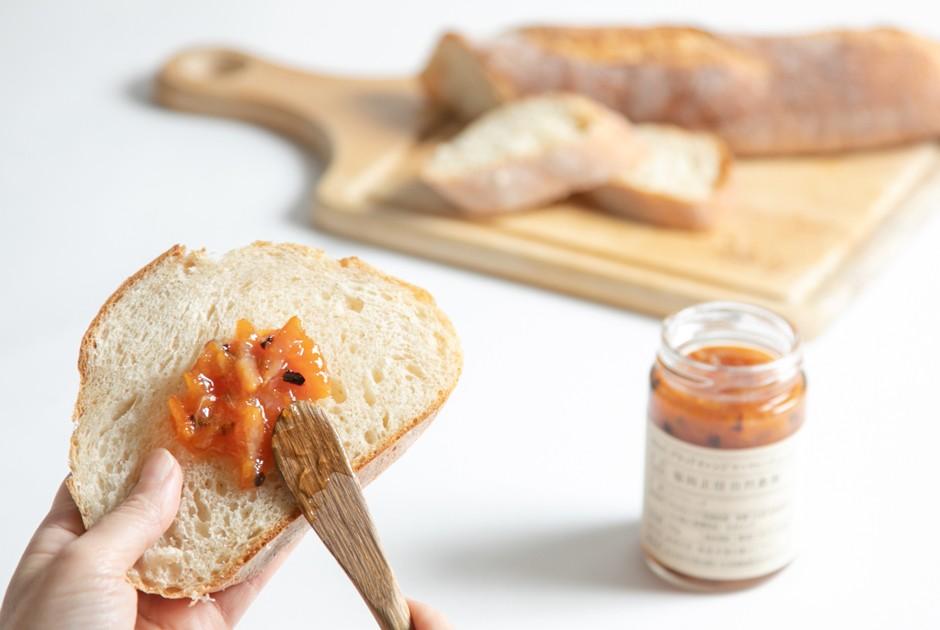 ブラッドオレンジマーマレードをパンに塗っている